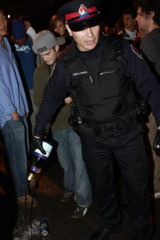 A Kingston Police Force officer pours out a bottle of wine during last year's Fauxcoming.