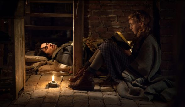 Sophie Nélisse and Ben Schnetzer bond in the basement, a place of protection from the Nazi regime.