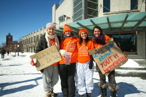 Volunteers stand outside of Stauffer Library to raise awareness about homeless youth.