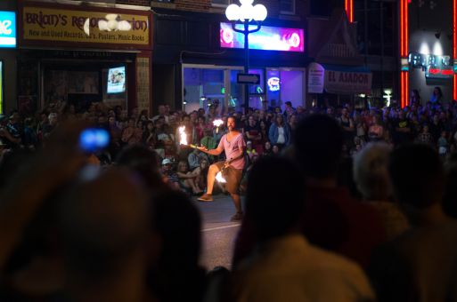A street performer juggles flames for the crowd at Kingston's Buskerfest.
