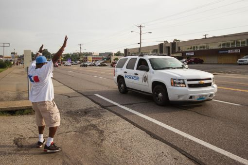 "A protester in Ferguson, Missouri chants ""Hands up, don't shoot."""