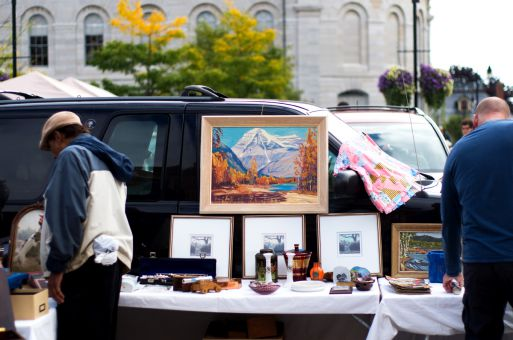 A collection of various pieces of framed visual art at the market.