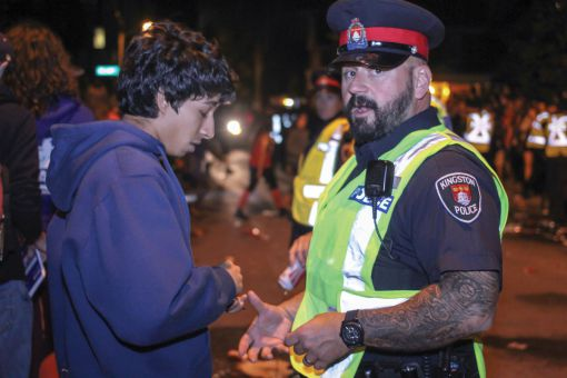A KPF officer speaks to a student on Aberdeen St. in 2013.