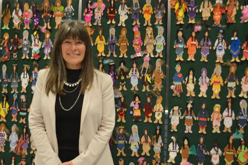 Kiwala, in front of a display of dolls that represent missing women.