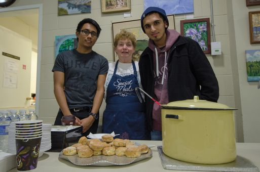 A chef, middle, at St. Andrew's Presbyterian Church and interfaith students from Queen's serving meals. Reyhan Viceer, right, is the chair of the Queen's University Muslim Students Association.