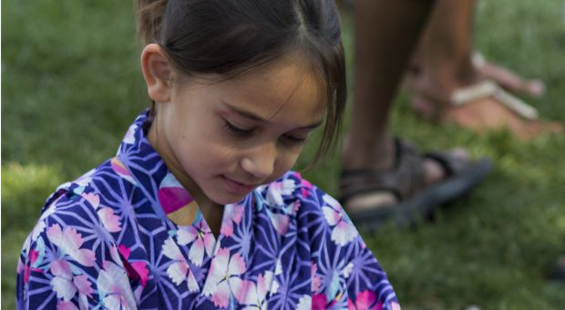Young girl sits on the grass at the lakeside during the Multicultural Arts Festival.