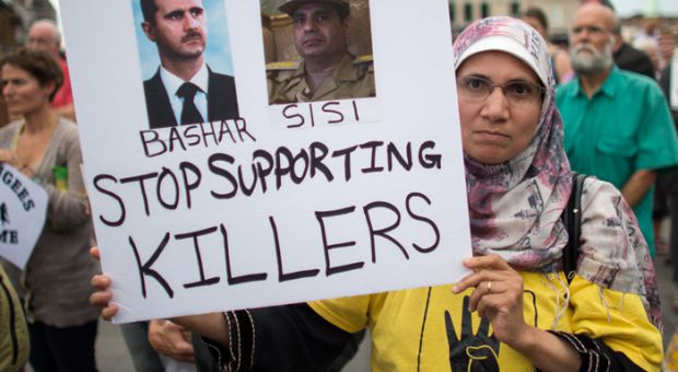 "A woman holding a sign that reads ""Stop Supporting Killers"", with a picture of Bashar and Sisi"
