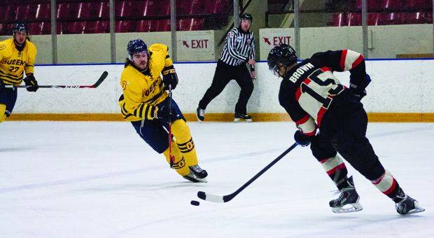 Taylor Clements (left) fights for the puck against Carleton.