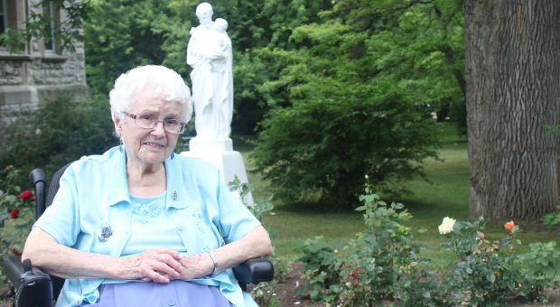 Sister Anna smiles beside the only tree older than she is at the Motherhouse.