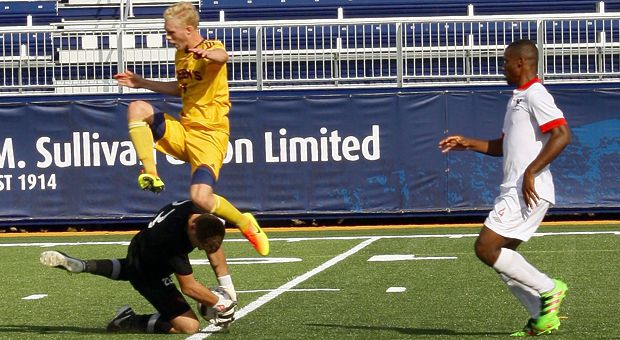Forward Jacob Schroeter (left) jumping over the Carleton keeper