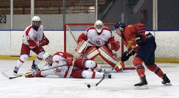 Alex Stothart (right) with the puck in front of the RMC net.