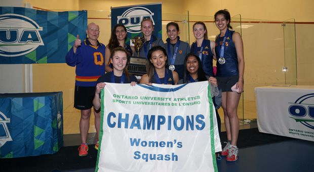 The women's squash team pose with their championship banner.