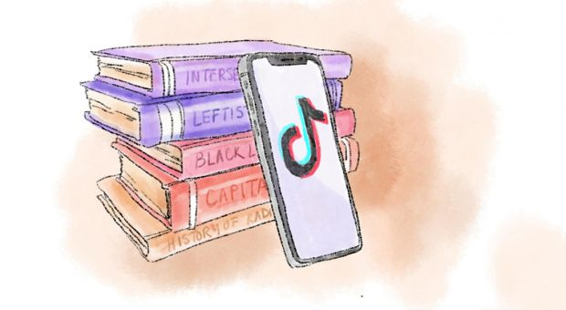 A phone with TikTok leaning against a stack of textbooks