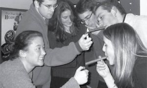 "Outgoing AMS executives (from left to right) VP (University Affairs) Mori, VP (Operations) Minns and President Carman light cigars for incoming President Heisler, VP (Operations) Bonikowski and VP (University Affairs) Cocker. Team HBC won the student vote in 2000 with a campaign tagline: ""The JDUC sucks!"""