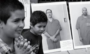 Ibrahim (left) and Yusuf Mahjoub, sons of Mohammad Mohjoub, ask for their father's release from prison next to portraits of other detainees during a protest outside Prime Minister Stephen Harper's office in Ottawa Monday June 12, 2006. Mahjoub has been held without charge on a security certificate since 2000.