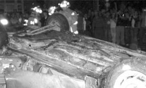 Firefighters inspect the flipped car on Saturday night.
