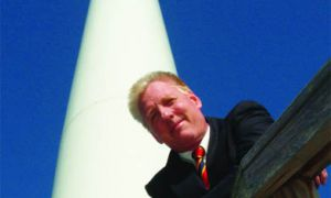 Ian Baines, Sci '74 and a driving force behind the upcoming Wolfe Island wind farm, stands in front of a wind turbine on display at the Canadian National Exhibition. Those scheduled to be erected on Wolfe Island in 2007 would be similar, but smaller.
