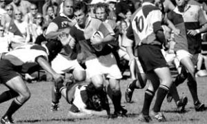 "John ""Moose"" Enright, a third-year second row player, scatters the ferocious Badger defence."