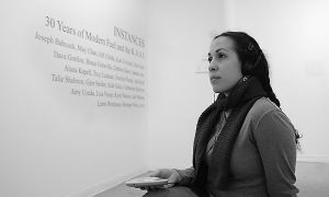Modern Fuel's administrative director Jessica Rovito listens to the oral history of the gallery and watches the sign-language translation that is set as part of the show Instances.