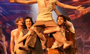 Cast members lift Andrew McWilliams during one of Hair's free-flowing dance numbers.