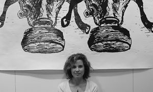 """Artist Jacqueline Collomb poses in front of a woodcut titled """"Gas Mask."""""""