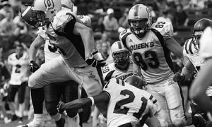 Queen's running back Mike Giffin hurdles Laurier free safety Courtney Stephen Saturday as teammate Scott Stinson (83) looks on. The Gaels beat Laurier for the first time in five years.