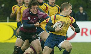 Gaels' centre Zach Pancer is pulled down by McMaster's Sam Roberts Saturday in Markham.