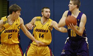Queen's forward Mitch Leger (14) and guard Tim Boyle defend against Laurier's Justin Golob Saturday night at Bartlett Gym. The Gaels lost 97-84 to the Golden Hawks.