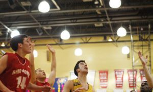 Gaels Pat Beswick (9) and Alex Murphy (11) go for a rebound against RMC's James Byun (10) and Simon Dakin Wednesday night at Bartlett Gym. Queen's won 72-33.