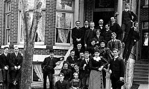 A group of Queen's students stand in front of Victor Hall boarding house in 1901.