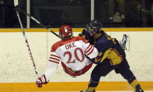 Queen's defenceman Brendan Bureau sends Paladins captain Jeffrey Oke to the ice during Saturday's 8-7 win in Gananoque.
