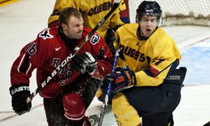 Queen's forward Brock Ouellet knocks Ravens' forward Chris Downey's helmet off during the Gaels' 4-1 loss at the Memorial Centre on Friday night. The Gaels take the ice on Sunday for the deciding game of the best-of-three series.