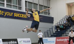Men's volleyball outside hitter, Joren Zeeman, unleashes a powerful serve.