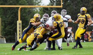 Gaels defensive backs Ben D'Andrea, right, and T.J. Chase-Dunawa, left, bring down a Marauders running back during Monday's game.