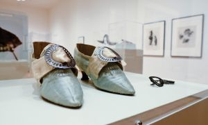 Adornment features six glass cases housing a variety of accessories including hats and embroidered purses from the 18th to 20th centuries. A pair of shoes (above) can be worn on either the left or right foot.