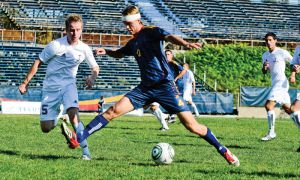 Second-year defender Dave Tom shields the ball from Toronto Varsity Blues players at Richardson Stadium on Sunday.