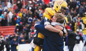 Backup quarterback Ryan Mitchell celebrates with injured starter Billy McPhee during the football team's 14-10 OUA quarter-final win at Richardson Stadium on Saturday.