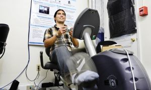 Hamilton Hernandez, PhD '14, demonstrates the Fit 'n' Fun game bike. The game was developed at the on-campus EQUIS Lab.