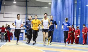 Some of the track and field team's distance athletes warm up at the Kingston Military Community Sports Centre indoor field house before a training session on Wednesday night.