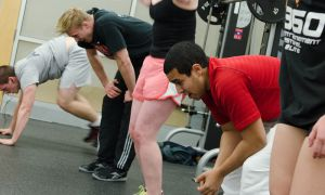 Storm Patterson, one of the leaders of CrossFit Queen's and second from left, and Badr Hefwani, second from right, work out together at the ARC. Patterson and his fellow organizers have put group workouts on hold until they can reach an agreement with Athletics and Recreation.
