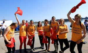 Queen's novice women's rowing crew celebrates with their opponents' shirts after winning the 500-metre sprint race at the Queen's-McGill Boat Race.