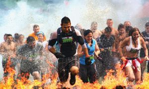 """Participants run among pits of blazing firewood for the """"Fire Walker"""" obstacle during the Tough Mudder obstacle race."""