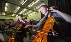 Katherine Knowles plays her cello during a practice with her peers.