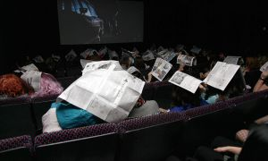 Audience members cover their heads with newspaper to mimic Janet as she runs through the rain.