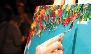 Schuyler Smith uses his palette knife at an Art Battle competition in Halifax.