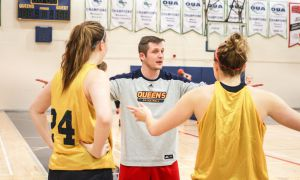 Assistant coach James Bambury counsels players at Wednesday's women's basketball practice.