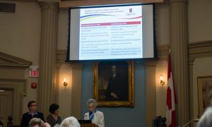 Caroline Davis presents a slide showing the differences between Queen's's first and second noise bylaw exemption applications.