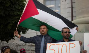 A man holds the flag of Palestine at a rally for Gaza.