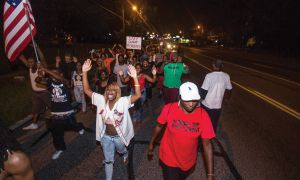 "Protestors in Ferguson, Missouri chant ""Hands up, don't shoot"" to emphasize Michael Brown was unarmed when shot by police."
