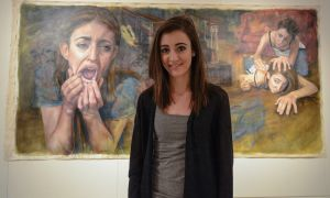 Morgan Campbell with her art piece Screwed in Union Gallery.